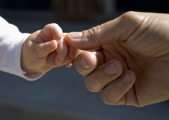 Baby's hand reaching for Father's hand