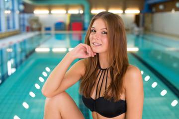Junge Frau posiert im Hallenbad