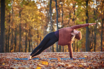 Beautiful young woman practices side bend yoga asana Vasishthasana on the wooden deck in the autumn park