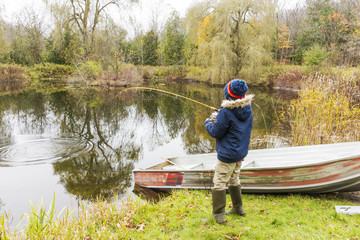 Young fisherman playing a fish in a pond