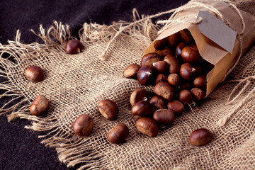 edible chestnuts - a bag of fresh, raw chestnuts sprinkled on the table