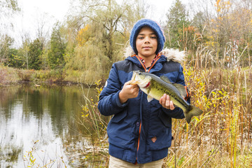 Young fisherman holding a bass he just caught on a fall day.