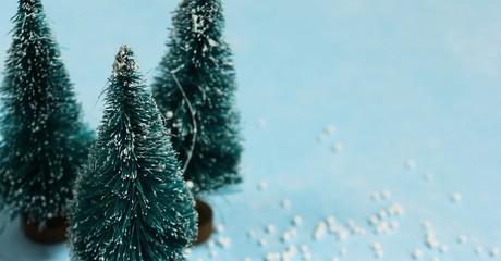 Christmas Background with mini Xmas trees on beautiful festive blue background