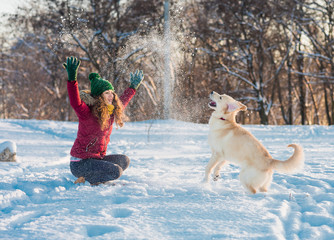 young woman plaing with golden retriever on winter walk.