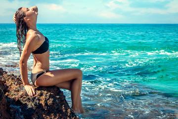 Sexy woman in bikini sitting on the rock