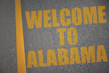 asphalt road with text welcome to alabama near yellow line
