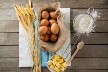 Eggs in wicker basket with wheat, cheese, and flour on wooden