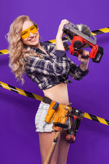 Pretty builder girl in chechered shirt, glasses and white shorts stand with electro saw