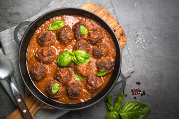 Meatballs in tomato sauce on a black background.