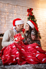 Happy romantic couple sitting on a carpet with Santa hats and red blanket hugged while man holding a gift for his girlfriend and looking each other for Christmas holidays.