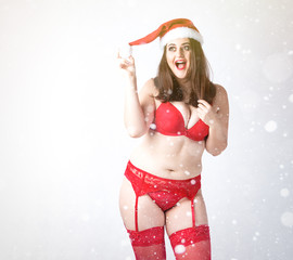 Happy cute fat Santa girl. Model in red lingerie and Santa hat. XXL woman celebrating Christmas and New Year. with snowfall