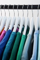 Colorful t-shirts arranged in a row on cloth rack