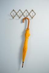 Yellow umbrella hanging on hook
