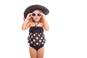 Attractive cute little girl in in black swimwear, white sunglasses and black hat