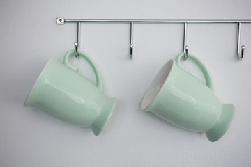 Close-up of mugs hanging on hook