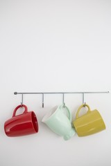 Colorful mugs hanging on hook