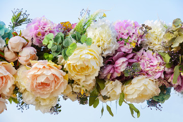 Decorative garland of artificial flowers - roses and hydrangeas.