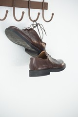 Pair of shoes hanging on hook