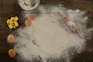 Flattened dough sprinkled with flour on a wooden table
