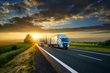 Fotobehang - Small truck overtakes heavy truck on the asphalt road in rural landscape at sunset with dark clouds