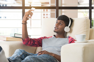 indian teenage male sitting on sofa listening to music