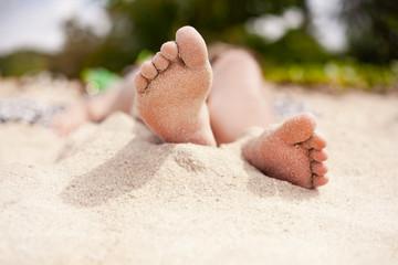 close up of beautiful young woman feet taking sun bath on the beach