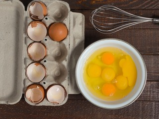 Shells of broken eggs in the container and the egg yolks in the mixer bowl and on a wooden table.