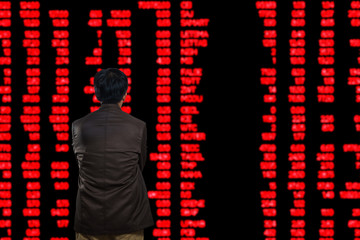 Asian Man or Male Looking at Stock Trading data on Display Board at Stock Exchange Market as Business financial investment concept.