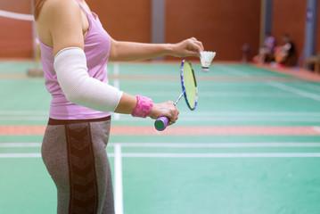 injured woman wearing sportswear  painful arm with gauze bandage  holding badminton racket standing on badminton court