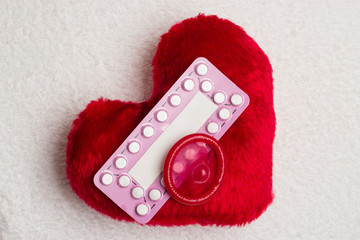 Oral contraceptive pills condom on red heart