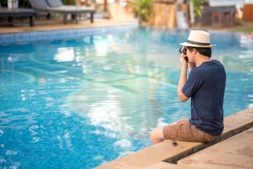 Young Asian man sitting on the edge of swimming pool and taking photo with his camera at resort, relaxing time and summer holiday vacation concepts