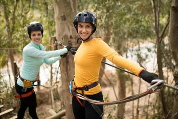 Friends enjoying zip line adventure in park