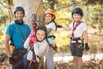 Kids enjoying zip line adventure on sunny day