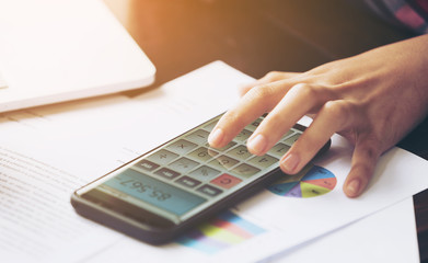 image of Hands woman or female accountant or banker making doing finances and calculate Debt and profit of fund business or about cost with smartphone on desk. Financing Accounting and economy Concept