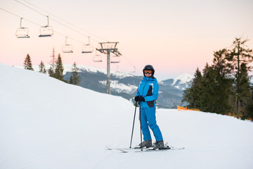 Young beautiful female on ski holiday in mountains looking at the camera and smiling. Woman at ski resort wearing helmet, blue ski suit and goggles.