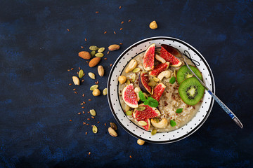 Delicious and healthy oatmeal with figs, nuts, kiwi and seeds. Healthy breakfast. Fitness food. Proper nutrition. Flat lay. Top view.