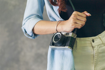 Young hipster woman photographer hand holding a retro film camera on cement wall background, vintage tone
