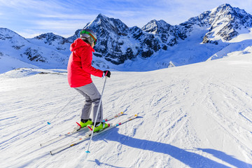 Fototapete - Girl on skiing on snow on a sunny day in the mountains. Ski in winter seasonon, the tops of snowy mountains in sunny day. South Tirol, Solda in Italy.