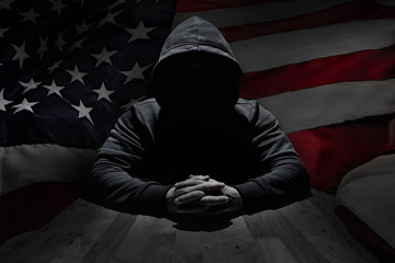 Concept hacker at work with usa flag on background
