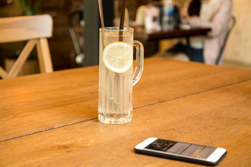 Health care fresh lemon juice drink with cell phone on wooden table