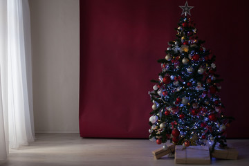 Christmas tree with presents on a red burgundy background