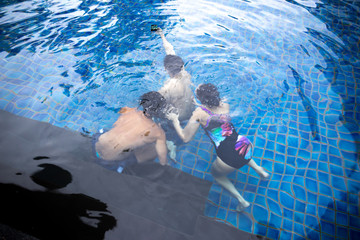 Group of friends taking selfie under the water in swimming pool resort with waterproof cell phone