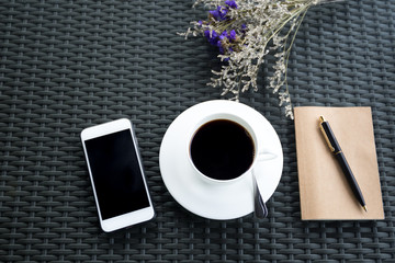Top view of cell phone and coffee with  flowers with notebook and pen
