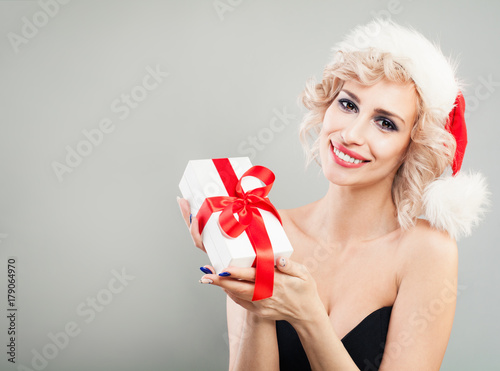 e0b5f5257b413 Happy Woman Christmas Concept. Xmas Model in Santa Hat holding White Christmas  Gift Box with Red Ribbon. New Year or Christmas Concept