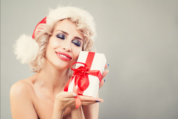 48d200c3b2ffc Christmas Gift Concept. Christmas Woman in Santa Hat with White Gift on  Banner Background.