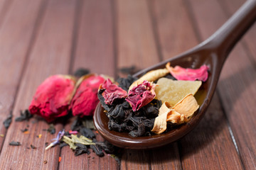 Composition of natural tea with a rose. Macro photo of tea petals on a ceramic spoon with a  rose. Tea with the ingredients of flowers and rose tea located on a wooden Board.