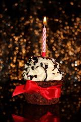 красивый праздничный фон с шоколадным кексам и красной лентой на блестящем фоне