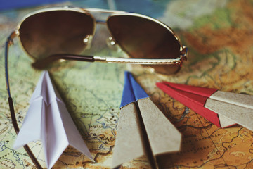 dark glasses and paper planes on the map, the concept of tourism