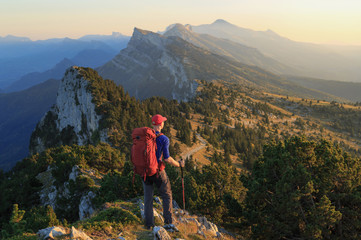 Fotomurales - A hiker looking over the mountains during the last light of the day. Vercors, France.