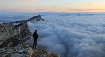 Fotomurales - A man looking over a sea of clouds in the mountains at dawn. Vercors, France.